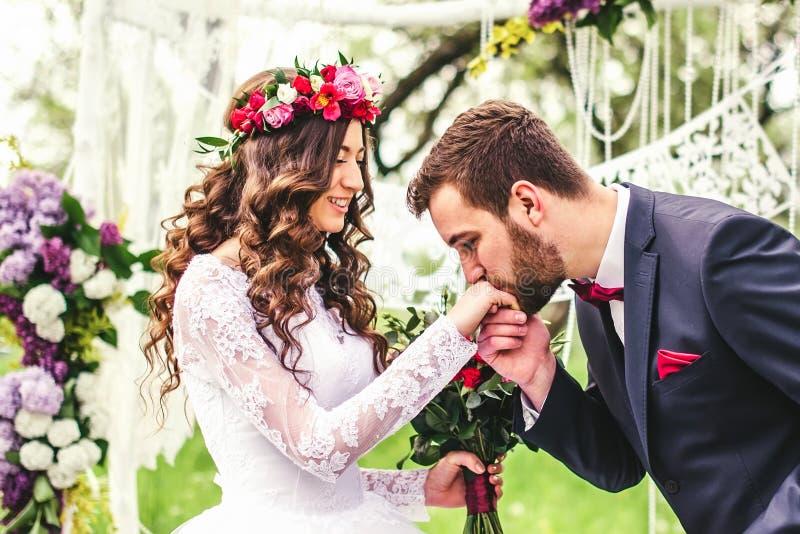 El novio besa la mano de la novia fotos de archivo