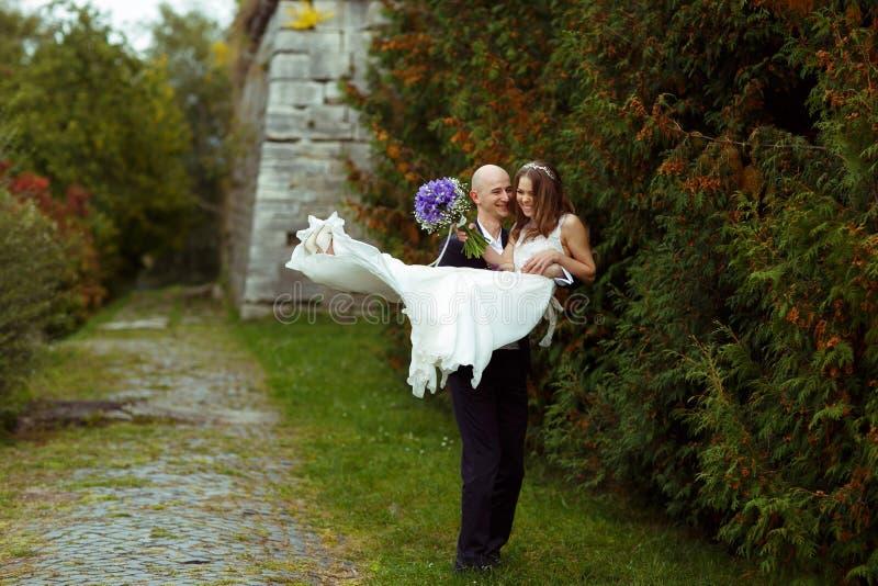 El novio camina con una novia en sus brazos a lo largo del parque imagenes de archivo