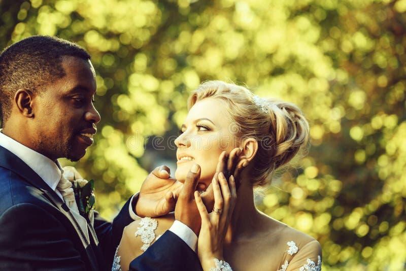 El novio cariñoso toca la cara de la novia adorable imagen de archivo
