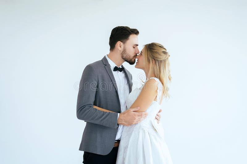 El novio con los pares rom?nticos de la novia es que se besa y de abrazo junto en el fondo blanco, pensamiento positivo en el d?a foto de archivo