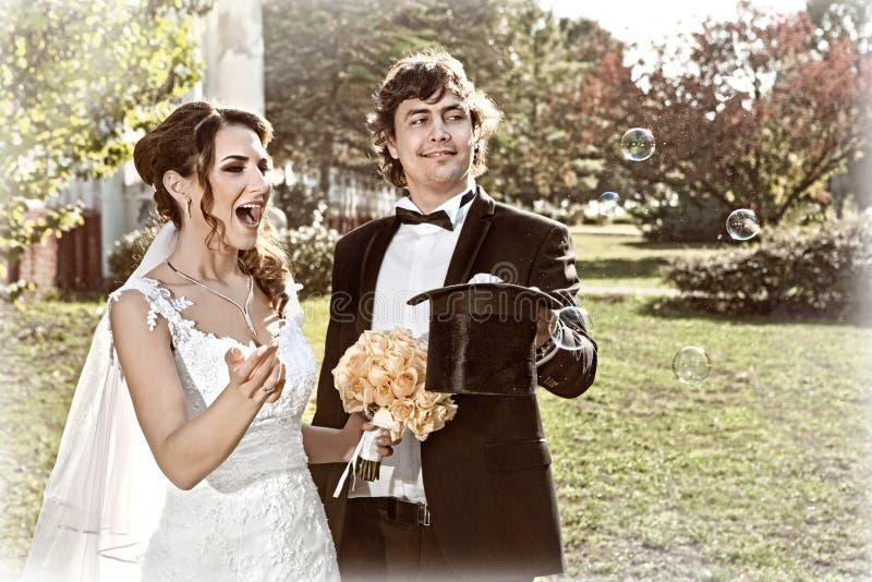 El novio conjura burbujas a la novia del sombrero foto de archivo libre de regalías