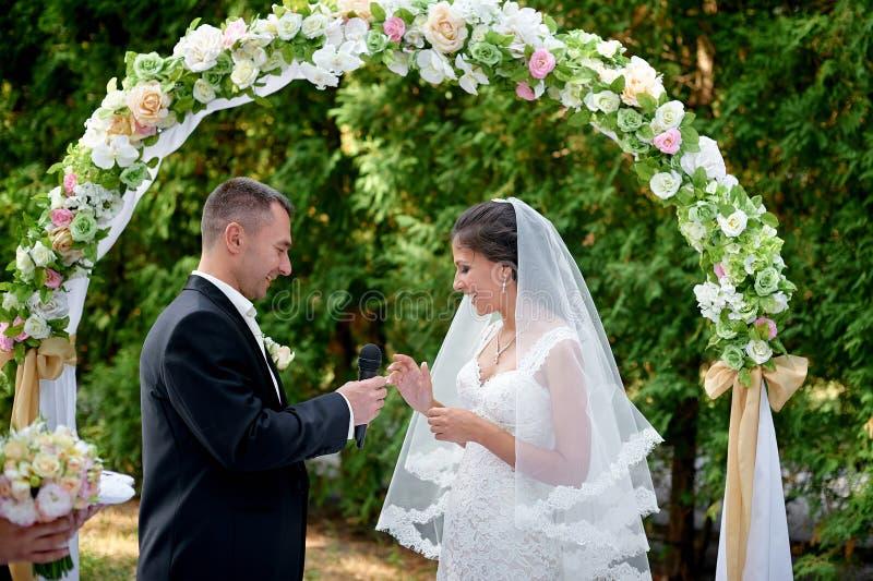 El novio de la novia viste un anillo en un finger en una ceremonia de boda foto de archivo libre de regalías
