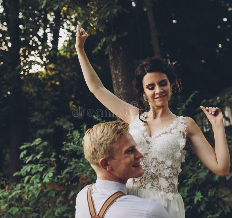 El novio detiene a la novia en sus brazos fotografía de archivo