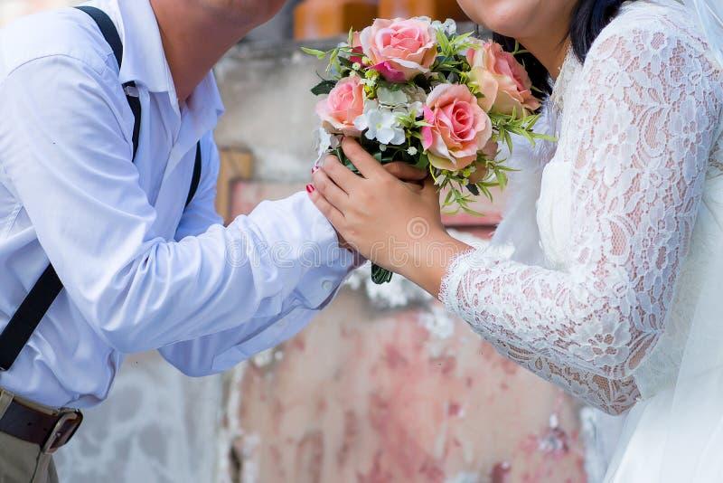 El novio elegante da el ramo de la flor a la novia hermosa, casandose concepto imagen de archivo libre de regalías