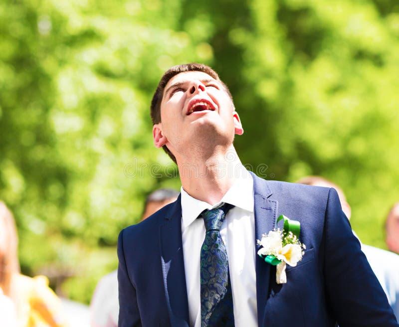 El novio en un traje azul con un ojal de flores y del verdor imagen de archivo libre de regalías