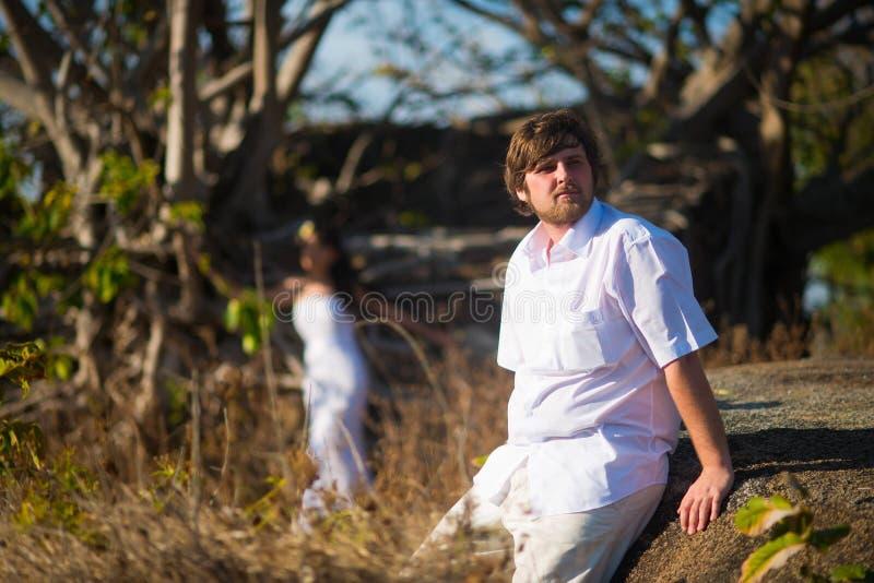 El novio en una camisa blanca se sienta en el medio de las plantas tropicales, y detrás de él es la novia foto de archivo