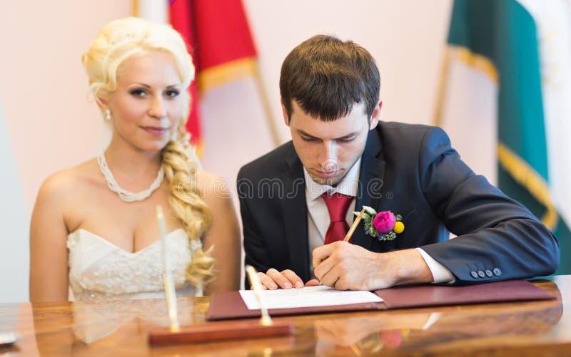 El novio escribe en el registro de la boda fotos de archivo libres de regalías