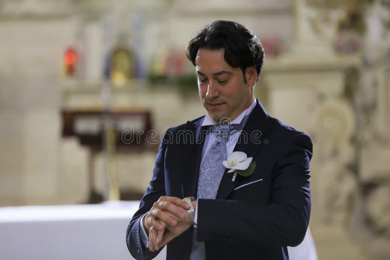 El novio espera a la novia en la puerta de la iglesia imagen de archivo libre de regalías