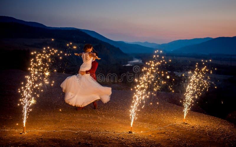 El novio está haciendo girar alrededor de su novia encantadora en las montañas adornadas con los fuegos artificiales ardientes imagen de archivo libre de regalías