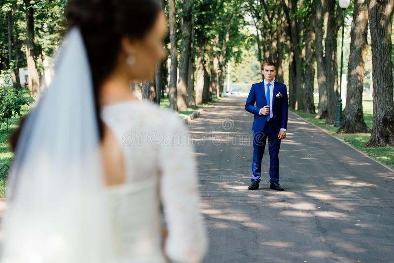 El novio está sosteniendo el cuello de su chaqueta al aire libre con la novia en la falta de definición delante de él imagen de archivo libre de regalías