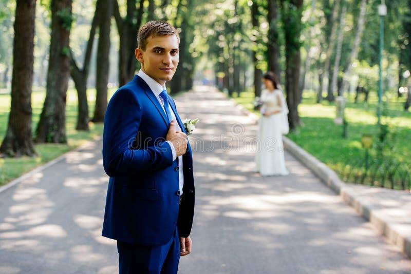 El novio está sosteniendo el cuello de su chaqueta al aire libre con la novia en la falta de definición en fondo imágenes de archivo libres de regalías