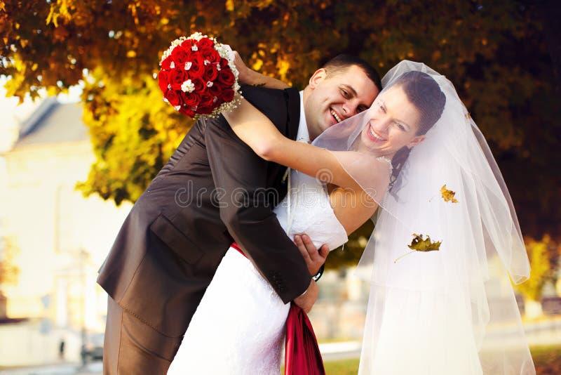 El novio feliz abraza a una novia debajo de árboles del otoño fotografía de archivo