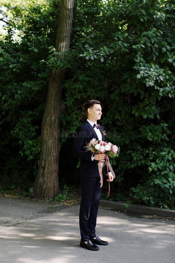 El novio feliz de la sonrisa está esperando a la novia con el ramo asombroso de flores en traje clásico con la corbata de lazo en imagen de archivo
