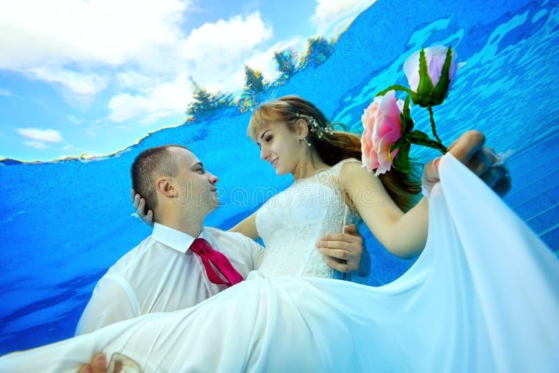 El novio feliz detiene a la novia en sus brazos subacuática en la piscina y la mira foto de archivo