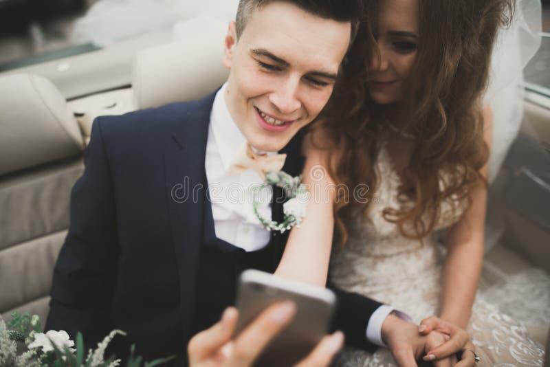 El novio feliz está tomando el selfie con su novia bonita el día de boda imagenes de archivo