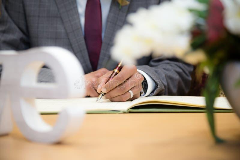El novio firma el certificado fotografía de archivo