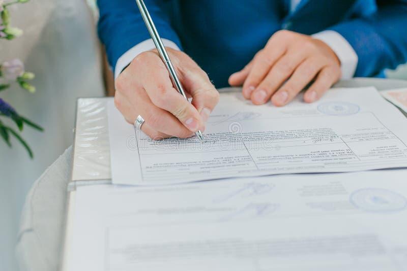 El novio firma los documentos del registro de boda Documentos de firma de la boda de los pares jovenes imagenes de archivo