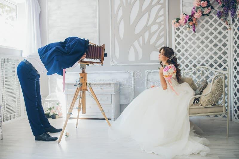 El novio fotografía a la novia en una cámara del vintage foto de archivo
