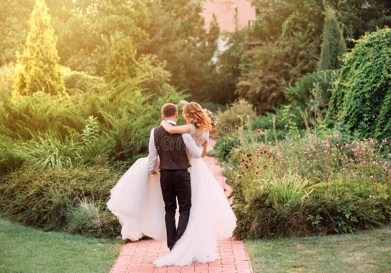 El novio joven en un traje lleva en brazos a su novia, llevando un vestido blanco lujoso magnífico largo, caminando en sorprender fotos de archivo libres de regalías