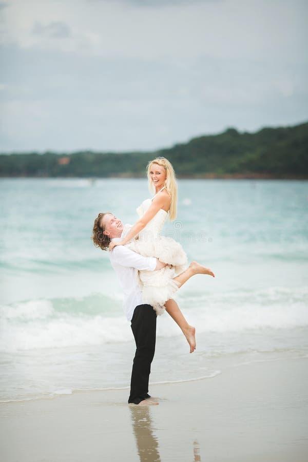 El novio levantó a su novia del mar recienes casados felices en una playa abandonada imágenes de archivo libres de regalías