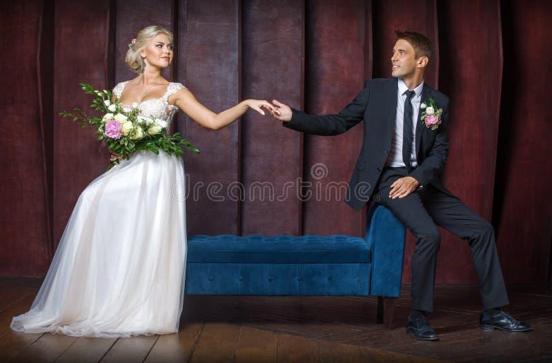 El novio lleva a cabo la mano de la novia fotografía de archivo libre de regalías