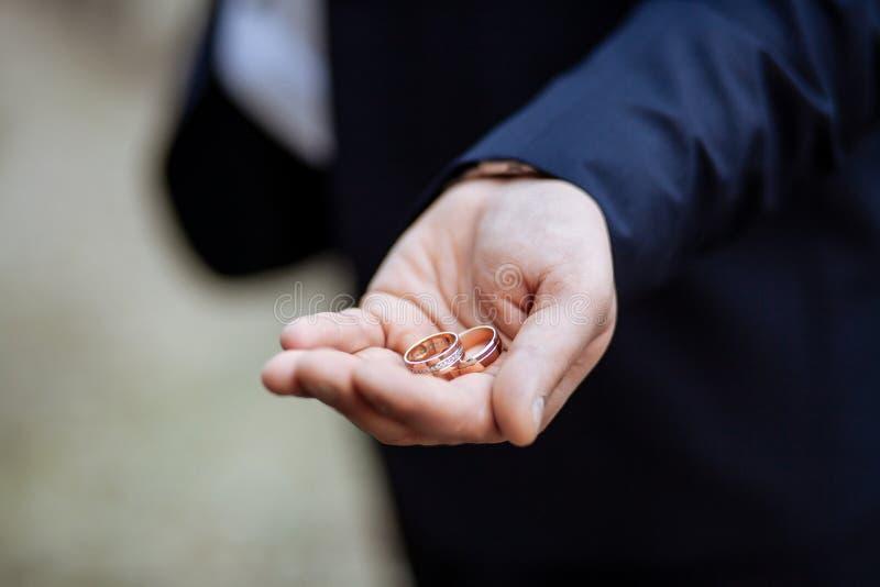 El novio lleva a cabo los anillos de bodas disponibles imagenes de archivo