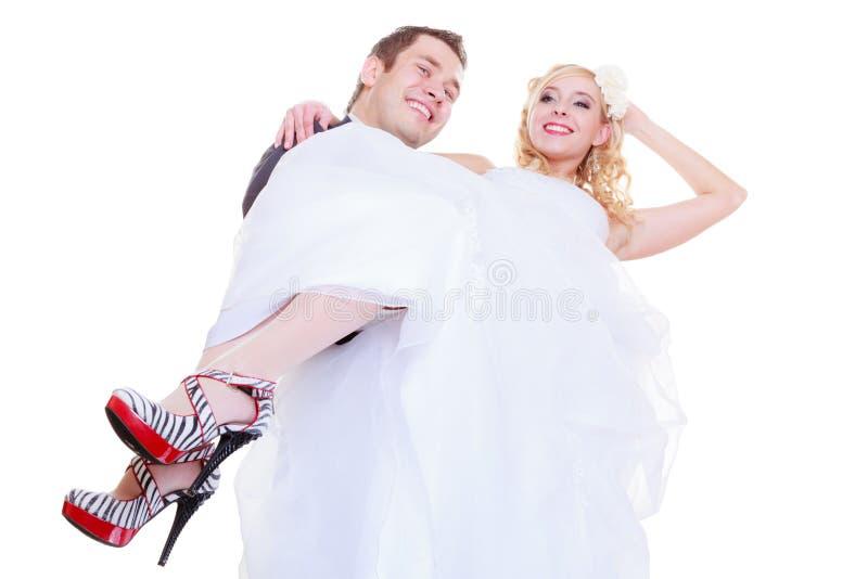 El novio lleva a la novia en sus brazos fotografía de archivo