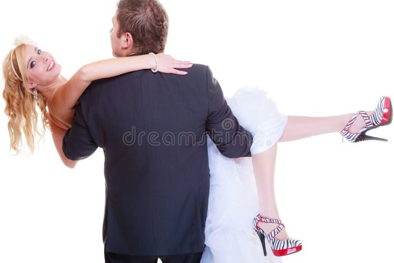 El novio lleva a la novia en sus brazos fotos de archivo libres de regalías