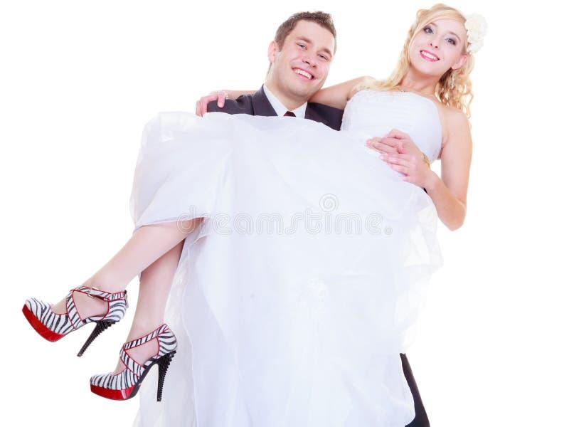 El novio lleva a la novia en sus brazos foto de archivo libre de regalías