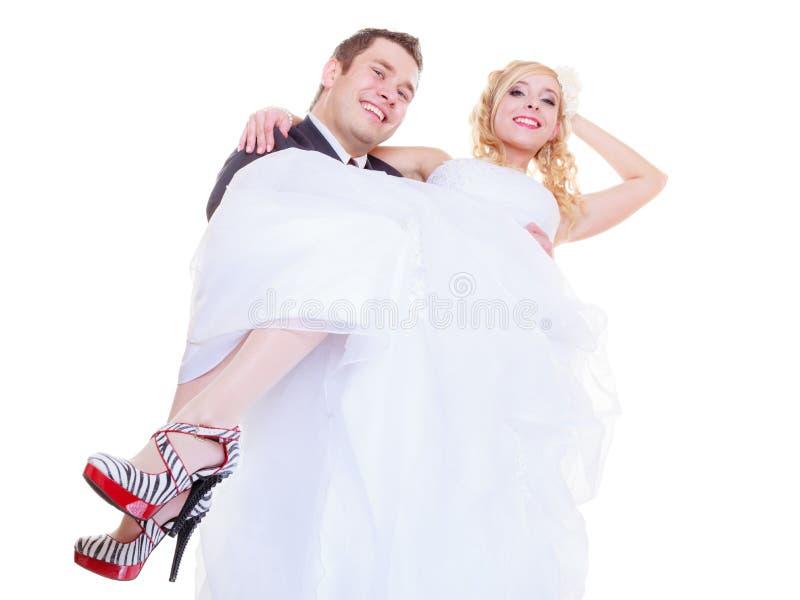 El novio lleva a la novia en sus brazos imagenes de archivo