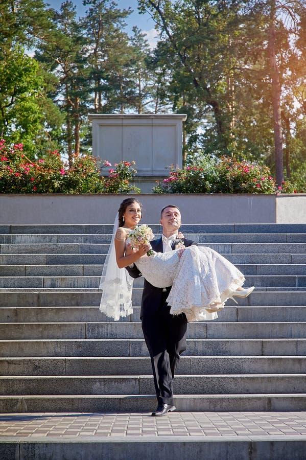El novio lleva a su novia en sus brazos en las escaleras imagen de archivo