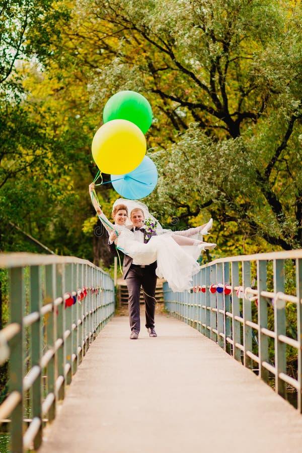 El novio lleva a su novia sobre el puente con los globos imagen de archivo libre de regalías