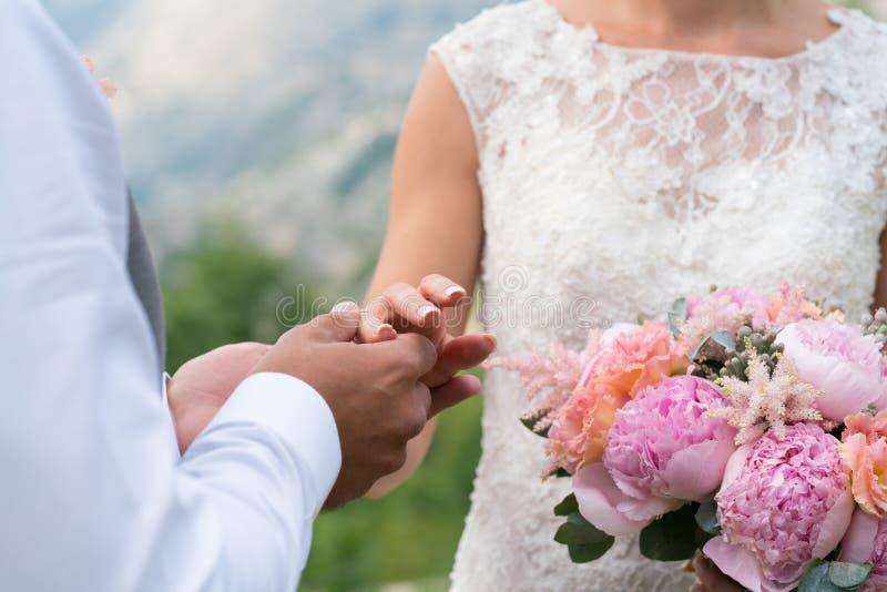 El novio pone el anillo en el finger del ` s de la novia imágenes de archivo libres de regalías