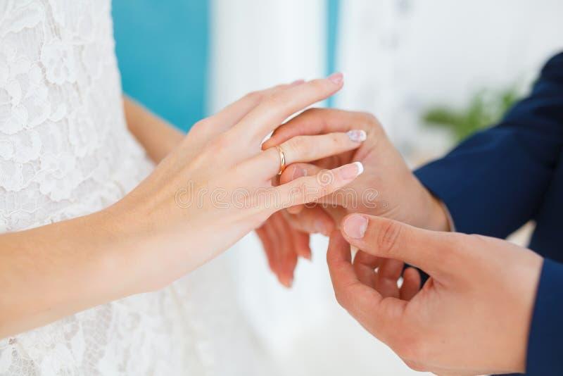 El novio pone cuidadosamente el anillo en el finger de la futura esposa foto de archivo