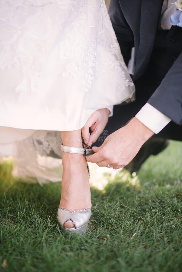 El novio pone a la novia en el zapato del primer del pie foto de archivo