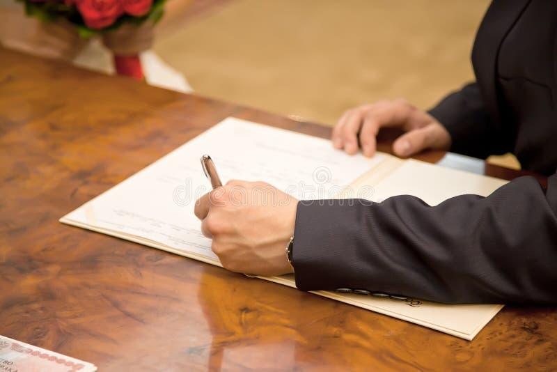 El novio pone su firma al certificado del documento de boda foto de archivo