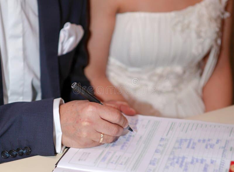 El novio pone su firma en el documento del matrimonio, foco selectivo foto de archivo libre de regalías