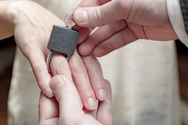 El novio pone un candado en el finger de la novia como concepto del matrimonio, demostrando el unfreedom foto de archivo libre de regalías