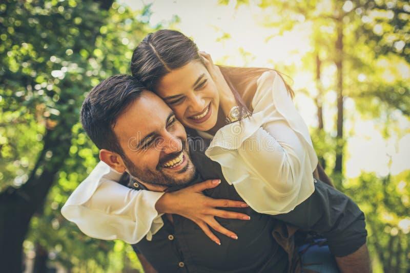 El novio que lleva a su novia encendido lleva a cuestas Estación de resorte fotografía de archivo libre de regalías