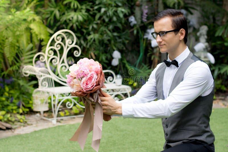 El novio se arrodilla abajo y sosteniendo un ramo para proponga la boda a la amiga en el jardín imagen de archivo libre de regalías