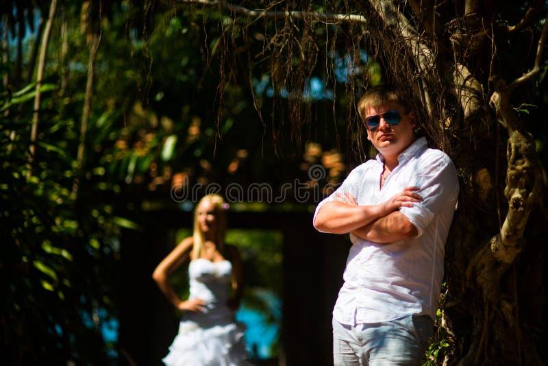 El novio se coloca cerca del árbol tropical, y detrás de él es la novia foto de archivo