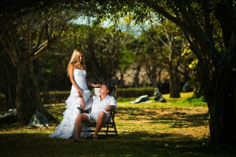 El novio se sienta en un césped en una silla en el medio de árboles tropicales, y la novia se coloca al lado de él foto de archivo