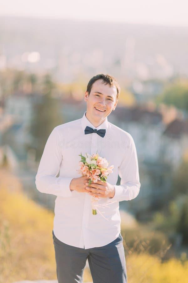 El novio sonriente de la morenita elegante en la camisa blanca con el arco azul sostiene el ramo lujoso de flores al aire libre imagen de archivo libre de regalías