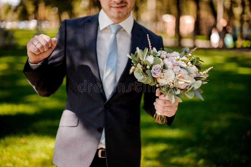El novio sonriente se vistió en un traje de la boda con las flores fotografía de archivo