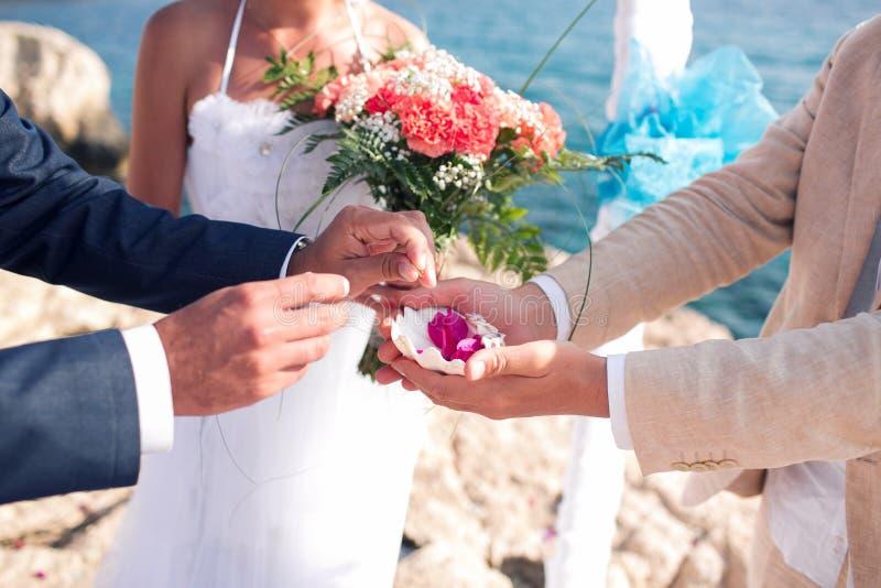 El novio toma el anillo Casandose en Chipre, novia y novio en un puente de piedra en Agia Napa arco y tabla para imagen de archivo