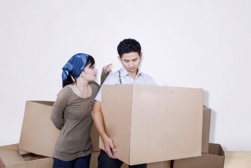 El novio trae la caja en blanco con la novia enojada imagenes de archivo