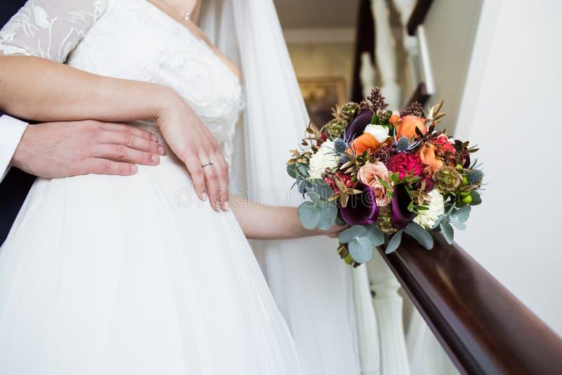 El novio y la novia con el ramo de la rosa del rojo se detienen las manos encendido foto de archivo