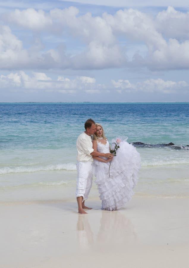 El novio y la novia en la playa tropical foto de archivo