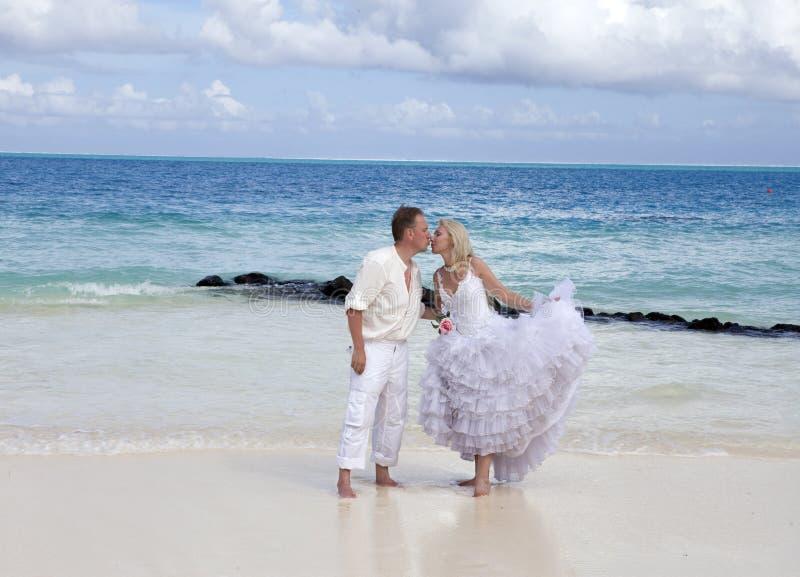 El novio y la novia en la playa tropical fotografía de archivo