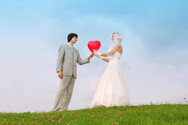 El novio y la novia guardan el globo en forma de corazón foto de archivo